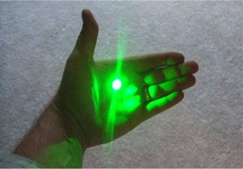 Green laser pointing at hand.