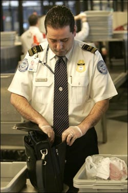 TSA employee looks inside laptop bag.